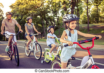 Family on bikes - Happy family is riding bikes outdoors and...