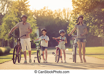 Family on bikes - Happy family with bikes outdoors. All are...