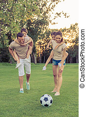 Family playing soccer - Beautiful happy family is smiling...