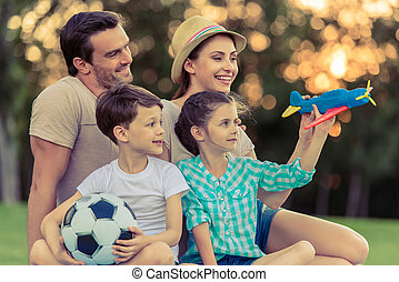 Family playing outside - Beautiful happy family is smiling...