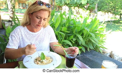 Woman eating pasta at the cafe - Middle aged woman in white...