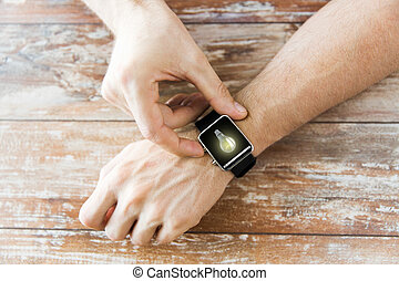 close up of hands with light bulb on smart watch - business,...