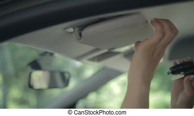 Woman hiding ignition key in car sun visor - Side view of...