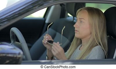 Charming young woman in car fastening seat belt - Side view...