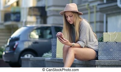 Woman shopping online using mobile phone outdoor Cheerful...