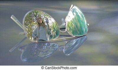Reflection in sunglasses of woman holding car keys -...