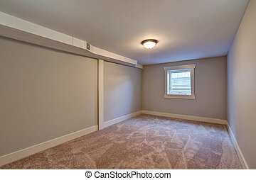 Empty room with beige carpet floor and small window...