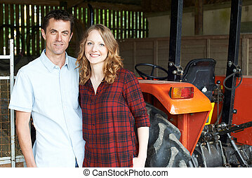 Portrait Of Farmers Standing In Barn With Tractor