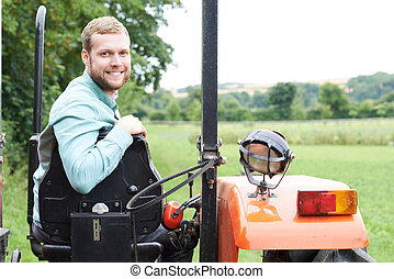 Portrait Of Farmer Sitting On Tractor In Field