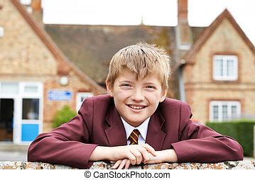 Portrait Of Boy In Uniform Outside School Building