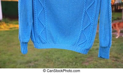 blue sweater hanging on the wire,dried clothes, knitted...