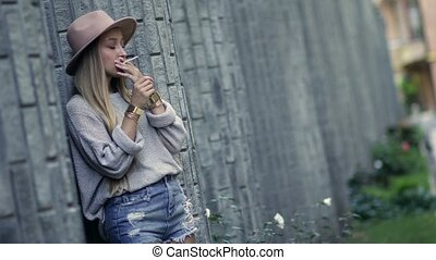 Woman smoking and leaning on the loft brick wall - Beautiful...