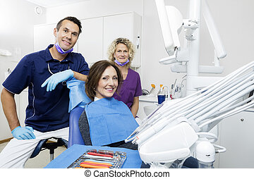 Smiling Patient With Dentist And Assistant At Clinic