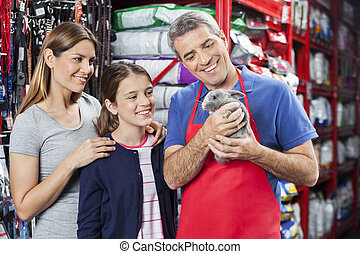 Salesman And Family Looking At Rabbit In Store - Happy...