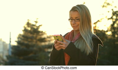 Woman sms texting on smartphone at park in the city