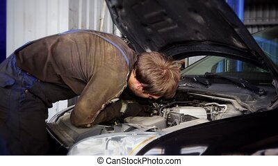 Auto mechanic repairing car starter system under hood. -...