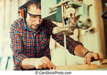 Close up of a young carpenter at work.He is using a bandsaw,...