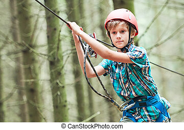 boy at climbing activity in high wire forest park -...