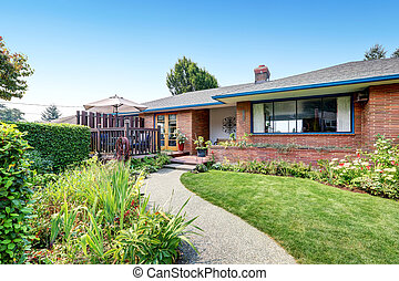 One level Red brick rambler house exterior with concrete...