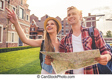 Beautiful young couple of travelers is using a map, looking...