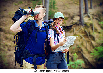 orienteering map - Hiking couple. Young people makes a hike...