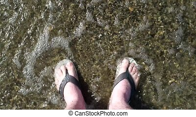 Man's feet washed by ocean waves and buries them in the sand. Top view