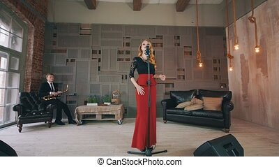 Jazz vocalist perform on stage. Saxophonist sitting in chair. Retro style dress