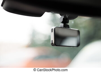 Car video recorder installed on front window, close up...