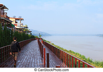Chiang Khan Boardwalk - A boy walks along a boardwalk next...