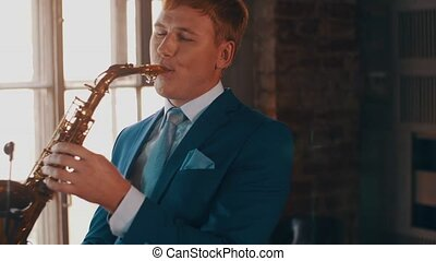 Saxophonist in blue suit play on golden saxophone. Live performance. Jazz artist