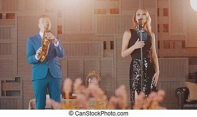 Jazz vocalist in glare dress and saxophonist in blue suit...