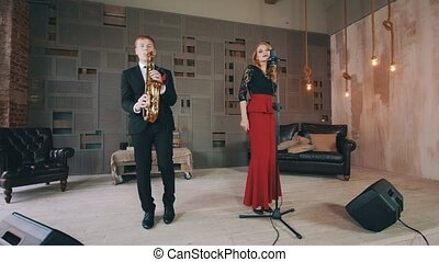 Jazz duet on stage. Saxophonist and vocalist. Retro style...