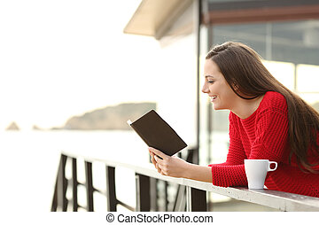 Woman reading an ebook on holidays - Side view of happy...