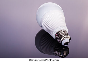 Led lightbulb on dark - a white satinated lightbulb shot...