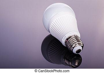 Led lightbulb on dark - a white satinated lightbulb shot...