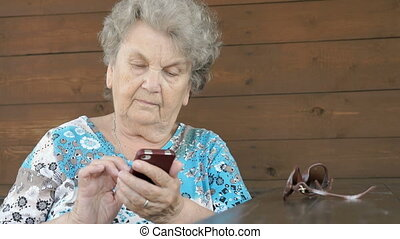 Old woman sitting at the table holds a smartphone outdoors