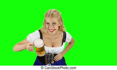 Woman in bavarian costume drinks a little of beer of glass....
