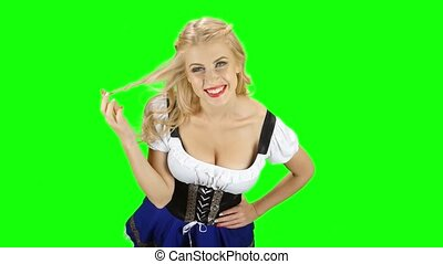 Bavarian woman flirty winds to finger a strand of hair and...