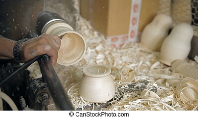 Making a Russian national toy on a lathe - A craftsman holds...
