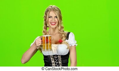 Girl in bavarian costume is enjoying a sip of beer. Green...