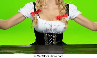 Woman in bavarian costume puts the glasses with beer. Green...