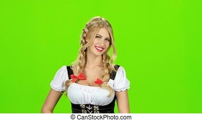 Woman in bavarian costume laughs and shows thumbs up. Green...
