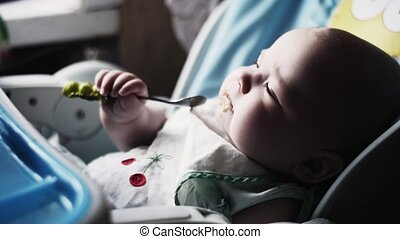 Mother feeding adorable baby at children table by puree....