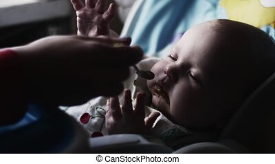 Mother feeding with spoon cute baby at children table by tasty puree. Motherhood