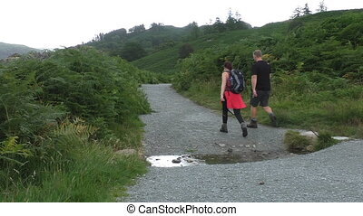 Young couple hiking - Young man and woman with backpack...