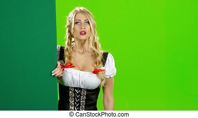 Girl in bavarian costume beckoning hand to her and waving...