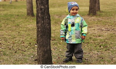 Cute little boyis standing near a tree in a park and smiling