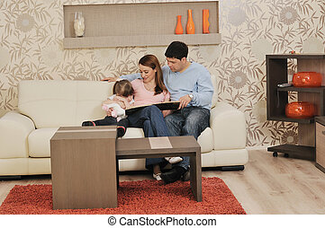 happy young family at home - happy young family relaxing in...
