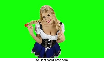 Girl in bavarian costume touches her hair and laughs. Green...