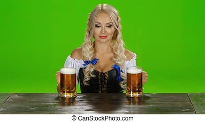 Bavarian girl takes on the table two glasses of beer nd shows thumbs. Green screen